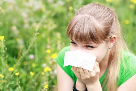 Jeune femme éternuements dans une prairie de fleurs. Concept: allergie saisonnière