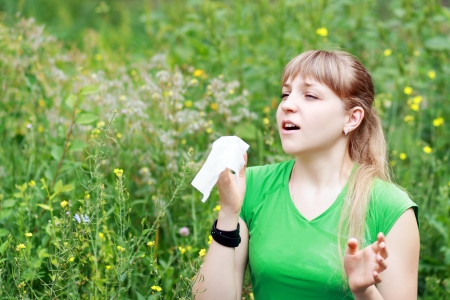Young woman sneezing in a flowers meadow. Concept: seasonal allergy