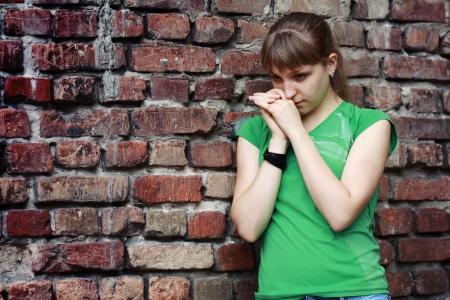 teenage problems: Mujer joven triste cerca de la pared de piedra. Colores oscuros depresivos. Problemas adolescentes