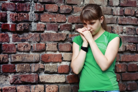 thoughtful woman: Sad young woman near stone wall. Dark depressive colors. Teenage problems Stock Photo