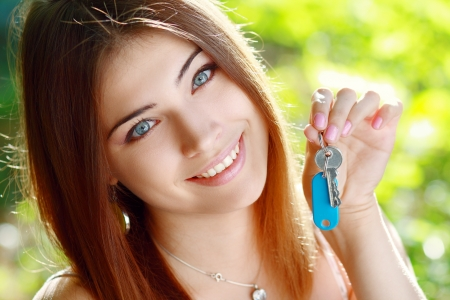 beautiful smiling young woman holding up a set of keys belonging to her house in her hand outdoor in green park photo