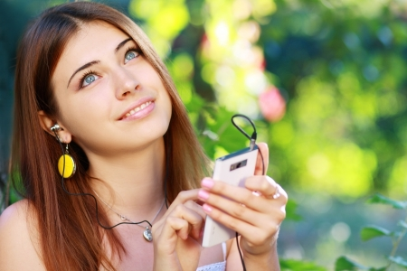 Close up portrait of a young woman using a smartphone to listen to music with her head phones, sitting outdoors in the city on a sunny day photo