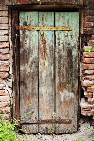 The Old Door with Cracked Paint Background and old bricks around it Stock Photo