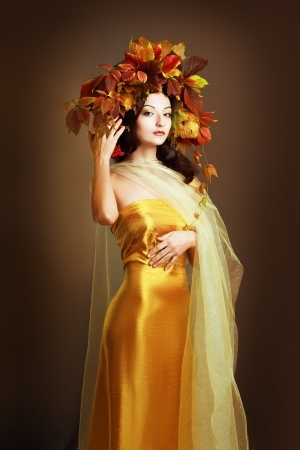 Autumn Woman close up. Beautiful makeup iover orange brown background. viburnum berries photo