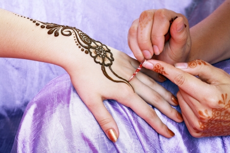 body paint: Image detail of henna being applied to hand Stock Photo