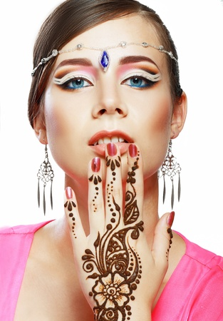 Beautiful girl face with perfect arabian make up with hand with detail of henna being applied to it isolated photo
