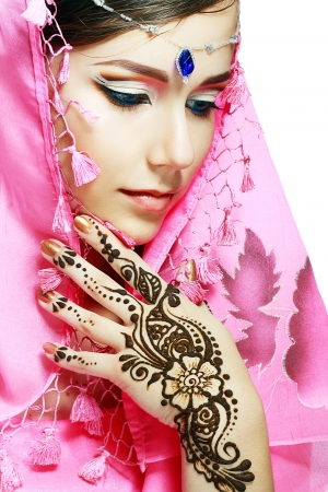 Beautiful girl face with perfect arabian make up with hand with detail of henna being applied to it isolated