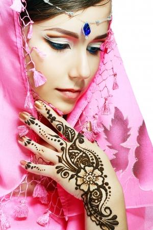 Mooi meisje met perfecte Arabische make-up met de hand met detail van henna wordt toegepast op het geïsoleerd