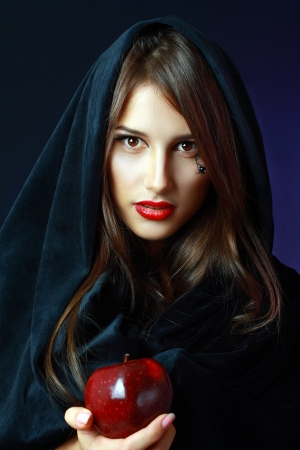 Halloween. Fashion portrait of witch or night vampire woman offering poisoned apple. Bright red lips photo