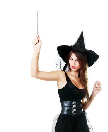wand: pretty young brunette witch hold magic wand in her hand poiting to copyspace