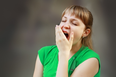 girl looking up: Yawning tired woman. Beautiful caucasian model isolated on white background.