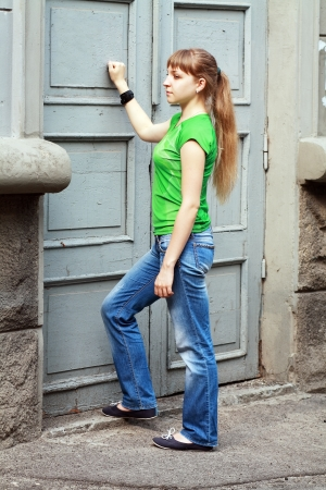 beautiful woman knocking the old door in the city