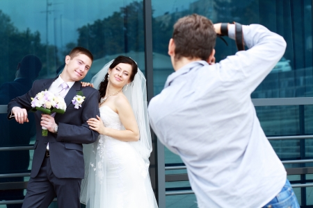 Wedding photographer in action, taking a picture of the bride and groom photo