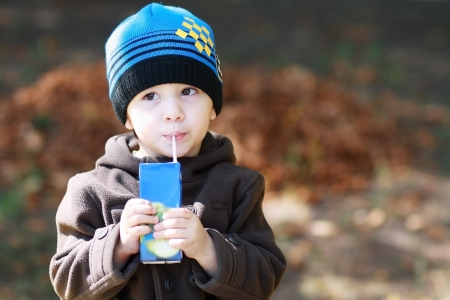 the sincerity: European two years old boy drinks juice and dreaming at the park