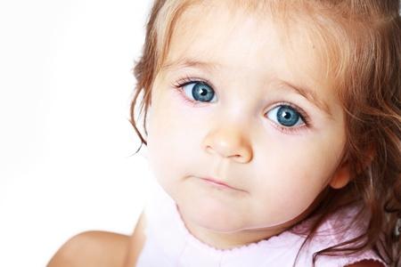Een jonge baby meisje is op zoek naar de camera met heldere blauwe ogen. Gebruik het voor een kind of ouderschap concept.