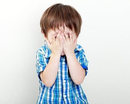 kleiner Junge für seine Augen mit den Händen hus Standard-Bild