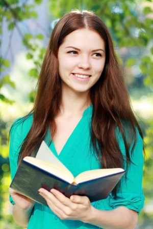 Charming long-haired student girl hold in hands book outdoor. Stock Photo