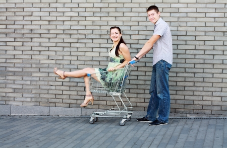 Handsome young man going out to shop pushing his carefree laughing wife along in a shopping trolley or cart as they have a fun day outdoor Stock Photo