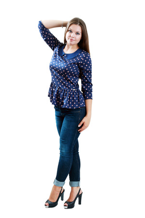 full-length portrait of beautiful plus size young brunette woman posing on white in blue jeans and court shoes  photo