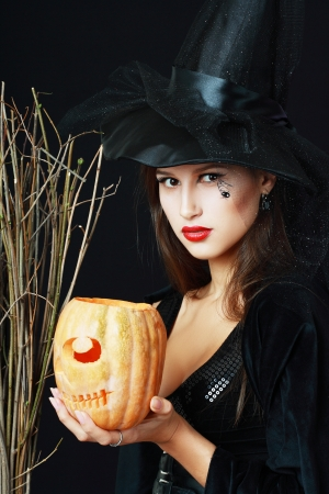 The serious brunette witch with a broom and pumpkin over black background in studio photo
