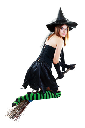 pretty sexy young brunette witch flying away on the broom photo