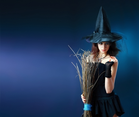 Charming halloween witch with broom over dardk blue background. Postcard concept, banner or flyer, lot of copyspace. Stock Photo