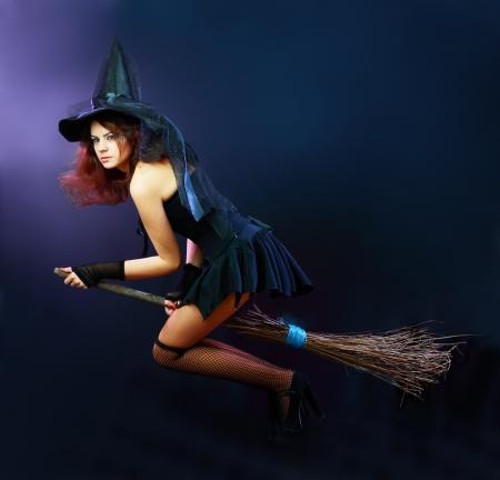 escoba: Sexy bruja morena volar en escoba en una oscura Foto de archivo