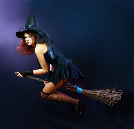 Sexy brunette heks vliegen op bezem op een donkere