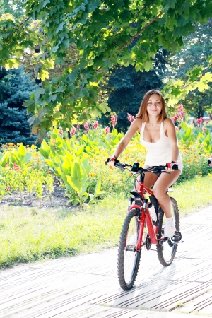 A beautiful young girl is riding on a bicycle in green summer park - Outdoors photo