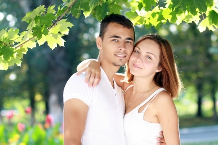 Close-up portrait of a charming couple smiling at the viewer in sunny summer or autumn day photo