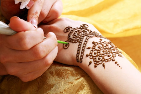 Image detail of henna being applied to hand over golden fabric Stock fotó - 22427938