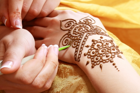 applied: Image detail of henna being applied to hand over golden fabric Stock Photo