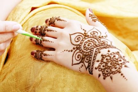 Afbeelding detail van henna wordt toegepast te overhandigen gouden stof Stockfoto