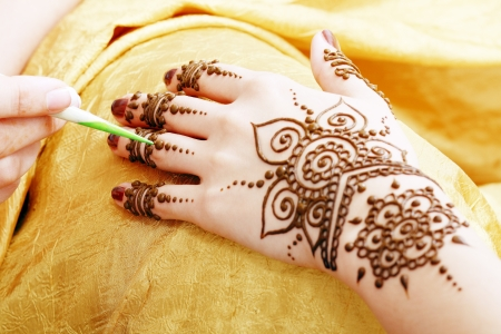 Image detail of henna being applied to hand over golden fabric Stock Photo