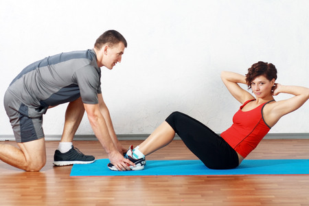 Portrait of a man helping a gorgeous woman to work out in gym
