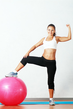 sporty fitness happy woman at the gym with a pilates ball photo
