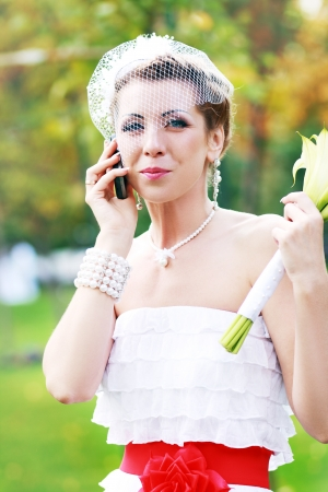 Happy bride talking over cell phone outdoor in autumn park photo
