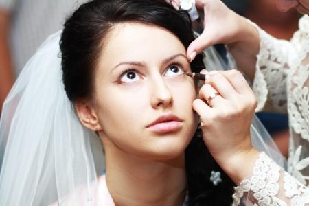 Junge schöne Braut Hochzeit Make-up von professionellen Maskenbildner anwenden