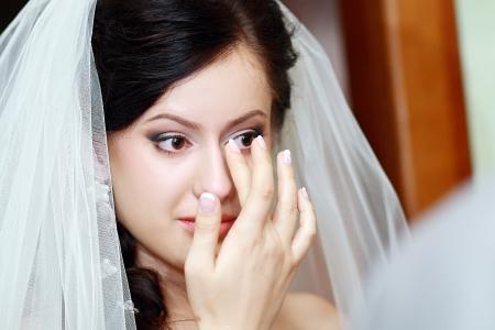 mujer llorando: Novia emocional que mira el espejo y enjuga las lágrimas