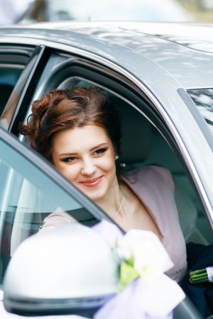 bridal makeup: attractive caucasian bride made sitting in car and smile Stock Photo