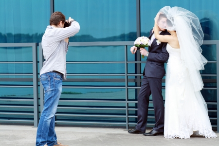 photographers: Wedding photographer in action, taking a picture of the bride and groom