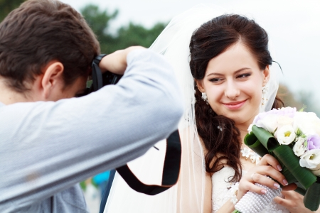 Wedding photographer in action, taking a picture of the bride posing at camera Standard-Bild