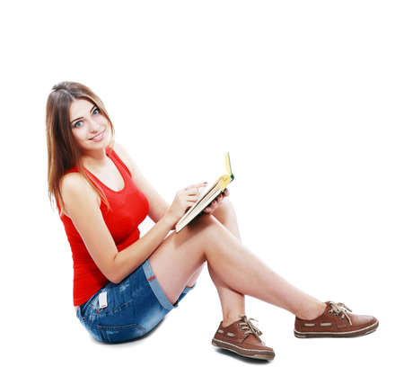 Friendly College student girl sitting and meditating with books down the floor isolated  photo