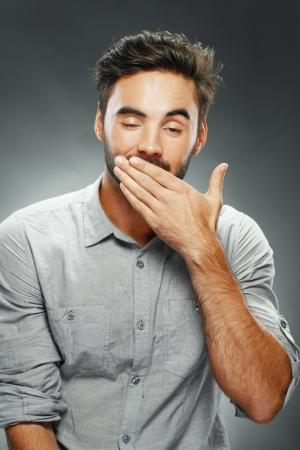 drowsiness: Young man yawning on grey studio background Stock Photo