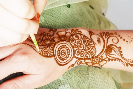 Image detail of henna being applied to hand over green fabric photo