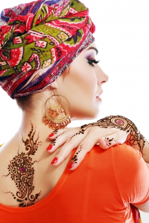applied: Beautiful woman arabian make up and turban on head with detail of henna being applied to hand and backt isolated