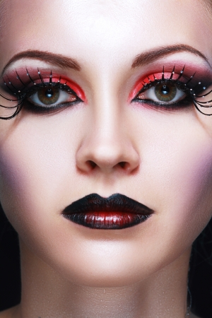 Close-up of beautiful woman face with Creative Fashion Art make up and eyelashes. Studio  photo