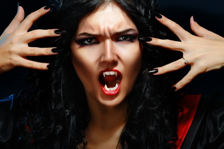 fangs: portrait of a woman vampire with fangs on a black background