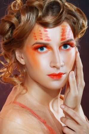 Autumn make up. Beautiful young woman with orange artistic visage and hairstyle photo