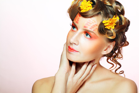 Autumn make up. Beautiful young woman with orange artistic visage and hairstyle on light pink background photo